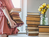 Young, cute woman and stack of vintage books