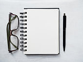Blank notepad page, pen and glasses. Greeting card