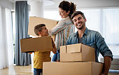 Happy young family unpacking cardboard boxes at new home