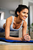 Happy fit young woman exercising at home. Healthy lifestyle, people, sport concept