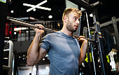 Man with weight training equipment exercising in sport gym club