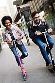 Two smiling business people driving electric scooter going to work.