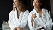 Lesbian couple relaxing and drinking tea in robes during wellness weekend