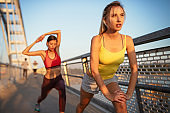 Beautiful happy women friends working out, exercising, running, jogging outdoor.