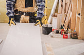 Male Contractor Holding Piece Of Drywall Material.