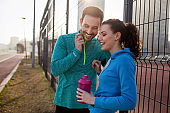 Beautiful young cheerful couple talking while resting after workout