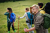 Group of friends trekking with backpacks walking in the forest