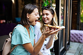 Portrait of young happy women eating pizza outdoors and having fun