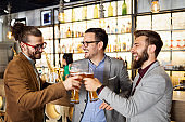 Young businessmen are drinking beer, talking and smiling while resting at the pub