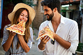 Couple eating pizza while traveling on vacation