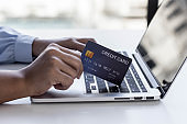 Hand holding credit card spending online payment using laptop in online shopping.