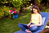 Young woman using laptop in the garden while working from home