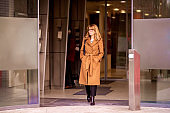 Shot of middle aged woman in beige coat with a bag walking out of the office building