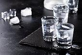 Frozen Vodka in shot glasses on black background, iced strong drink