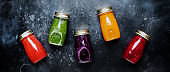 Food and drinks, healthy and useful multicolored vegetable juices and smoothies with ingredients in glass bottles. Panoramic banner with copy space