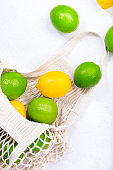 Organic lemons and limes in reusable eco-friendly string mesh bag. Zero waste, plastic free and sustainable lifestyle concept. White kitchen table background, copy space, top view