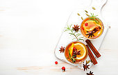 Winter healing hot tea with lemon, cranberries and warming spices, white background, copy space, top view