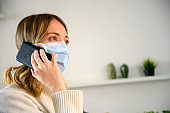 Woman wearing protective mask phoning from home