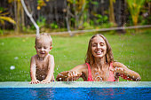 Happy child swimming with mother in tropical pool