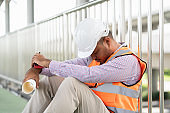 Tired depressed asian civil engineer man sleeping at working construction concrete road site holding paperwork and radio walkie talkie.