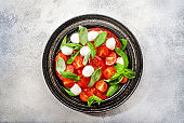 Tasty caprese salad with ripe red tomatoes and mozzarella cheese with fresh green basil leaves. Italian food. Top view