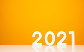 Happy new year 2021 mockup on white table and yellow background color. Celebrate with new year theme concept.