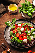 Caprese - italian salad with red tomatoes and mozzarella cheese with green basil leaves. Top view, wooden table