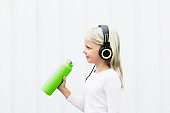 Young blond girl on white background drink fresh spring water from green reusable bottle. Healthy lifestyle in summer city.