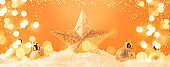Christmas orange background with golden star. New Year's decor. Christmas balls in snowdrifts and golden bokeh lights. Panoramic banner with copy space