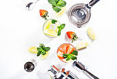 Fresh Mojito cocktail set with lime, mint, strawberry and ice in glass on white background. Summer cold alcoholic non-alcoholic drinks, beverages and cocktails. Steel bar tools. Copy space. Top view