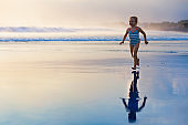 Child run with splashes by water pool along sea surf