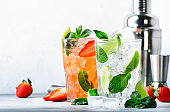 Fresh Mojito cocktail set with lime, mint, strawberry and ice in glass on grey background. Summer cold alcoholic non-alcoholic drinks, beverages and cocktails. Steel bar tools. Copy space
