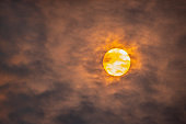 Telephoto view of rising sun through clouds of smoke and ash