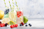 Berry and citrus fruit infused summer cold drinks in glass bottles on gray stone table background, copy space