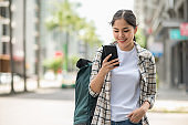 Young Asian beautiful woman travelers use her mobile phones to find travel locations and call for taxi transportation.
