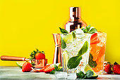 Fresh Mojito cocktail set with lime, mint, strawberry and ice in glass on yellow background. Summer cold alcoholic non-alcoholic drinks, beverages and cocktails. Steel bar tools. Copy space