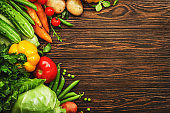 Assortment of fresh vegetables on frame wooden table background. Healthy organic food grocery concept. Copy space