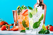 Fresh Mojito cocktail set with lime, mint, strawberry and ice in glass on b;ue background. Summer cold alcoholic non-alcoholic drinks, beverages and cocktails. Steel bar tools. Copy space