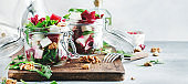 Beet salad with arugula, goat cheese and nuts, trendy salad jar, gray kitchen table. Panoramic banner with copy space