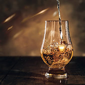 Scotch Whiskey without ice pouring out of the bottle, rustic wood background, copy space