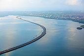 Aerial view of Bali Mandara toll road over sea gulf