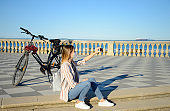 Young woman wearing protective mask with e-bike by using mobile phone by the sea