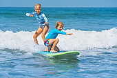 Two young surfers ride with fun on one surfboard