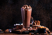 Glass of hot chocolate cocoa drink sprinkled with cocoa powder. Dark background. Winter food and drink concept with Copy space