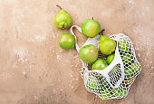 Fruits in reusable eco-friendly string mesh bag. Zero waste, plastic rejection and sustainable lifestyle concept. Brown kitchen table background, copy space, top view