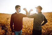 Two farmers in sterile medical masks greet their elbows on a wheat field during pandemic.
