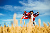 Fourth of July. Patriotic men with the national American flag in the field.