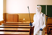 Portrait of man in protective hazmat suit with spray chemicals disinfecting school class. COVID-19.