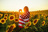 Beautiful girl with the American flag in a sunflower field.  Fourth of July.