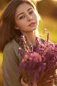 Portrait of a beautiful girl with a bouquet of lavender at sunset.